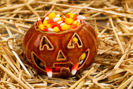 45935126 - front view of scary pumpkin with fangs filled with candy corn on straw. halloween concept.