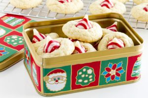 48150821 - homemade candy cane white chocolate cookies in christmas holiday cookie tin in front of wire baking rack filled with cookies